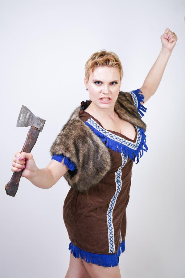有短发和正大小形象的坚强的妇女在有情感地积极地摆在的轴的原始猎人服装在白色ba 免版税库存图片