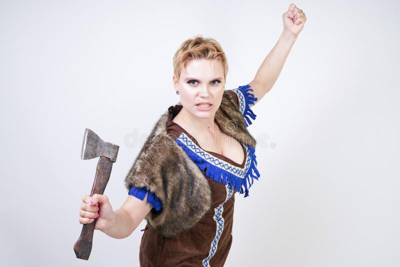 有短发和正大小形象的坚强的妇女在有情感地积极地摆在的轴的原始猎人服装在白色ba 图库摄影