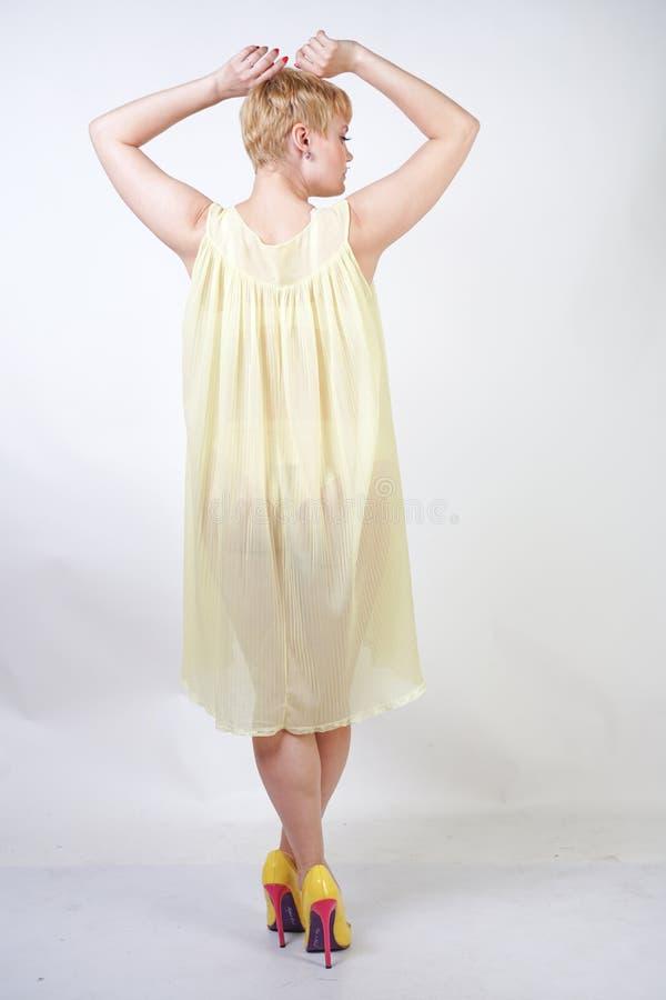 有短发的俏丽的年轻女人和穿透明女睡袍和摆在单独白色演播室背景的胖的身体 ?? 图库摄影