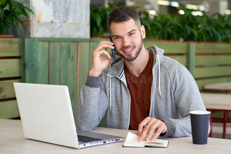 有短发的可爱的成功的年轻人浅黑肤色的男人和胡子坐在与膝上型计算机的一张桌上和谈话在电话 图库摄影