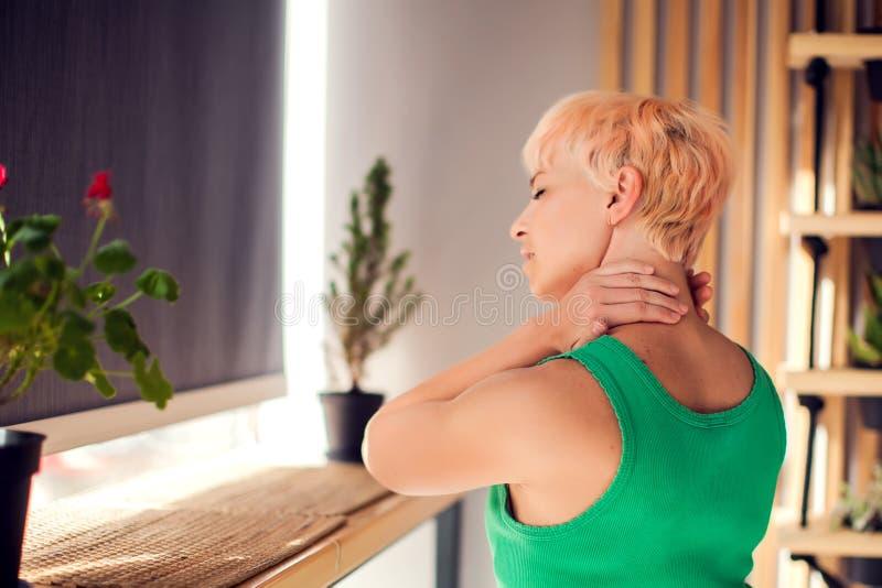 有短发的妇女以脖子和肩膀痛苦和伤害,后面看法,关闭 在遭受的肌肉的女性手 E 免版税库存图片