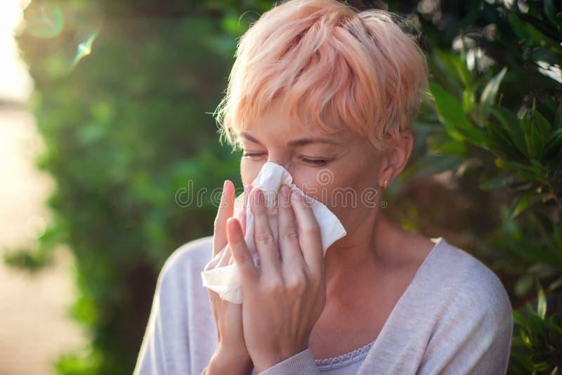 有短发的年轻女人打喷嚏入组织的 流感,过敏,鼻涕 o 免版税库存照片