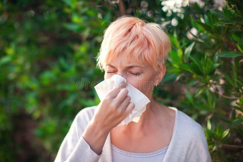 有短发的年轻女人打喷嚏入组织的 流感,过敏,鼻涕 o 免版税库存图片
