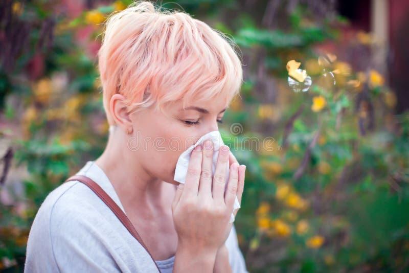 有短发的年轻女人打喷嚏入组织的 流感,过敏,鼻涕 o 库存图片