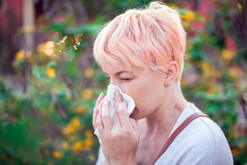 有短发的年轻女人打喷嚏入组织的 流感,过敏,鼻涕 o 免版税图库摄影