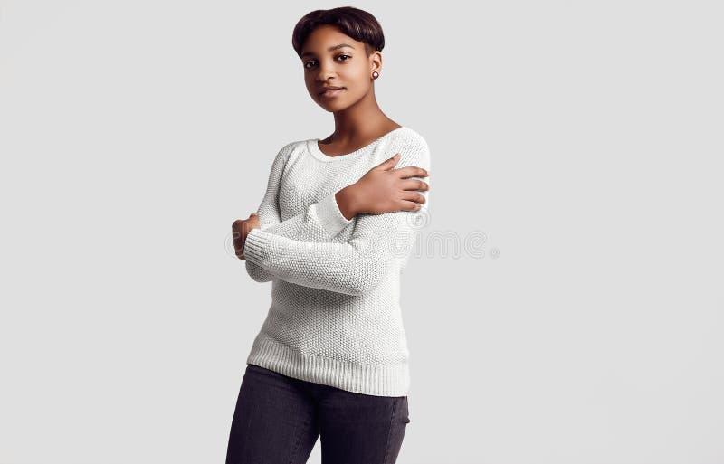 有短发的年轻美丽的行家黑色女孩在白色swea 免版税库存图片