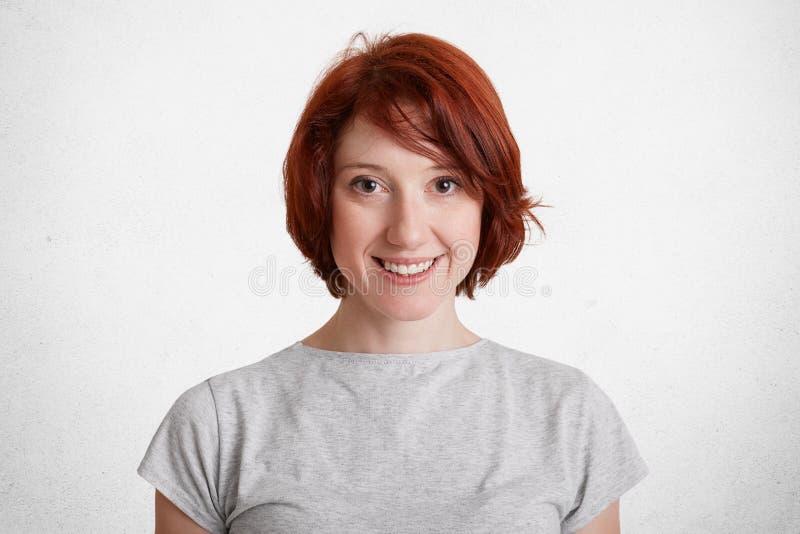 有短发的微笑的红发女性,穿戴随便,有正面微笑,高兴早晨好,被隔绝在白色具体ba 库存图片