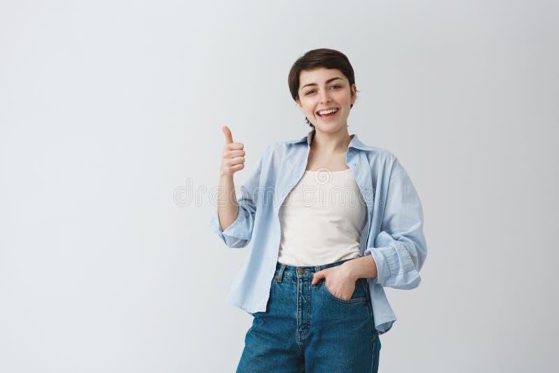 有短发的悦目年轻白种人女孩微笑与牙的,显示与愉快和高兴的赞许 免版税库存图片