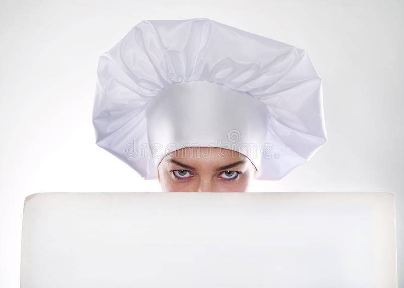 有短发的白肤金发的妇女在一位帽子和厨师有拿着一个白色广告牌的美好的微笑的 库存图片