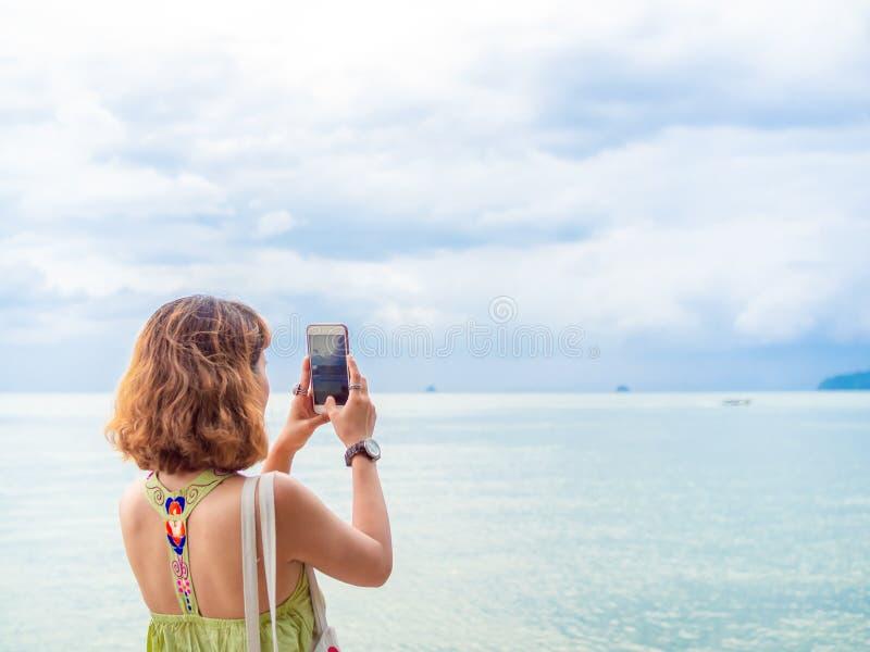 有短发的美丽的亚裔妇女使用智能手机采取照片海景观点 图库摄影