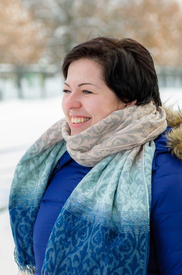 有短发的美丽的深色的女孩,摆在半轮的业余的模型室外在冬天穿衣 免版税图库摄影