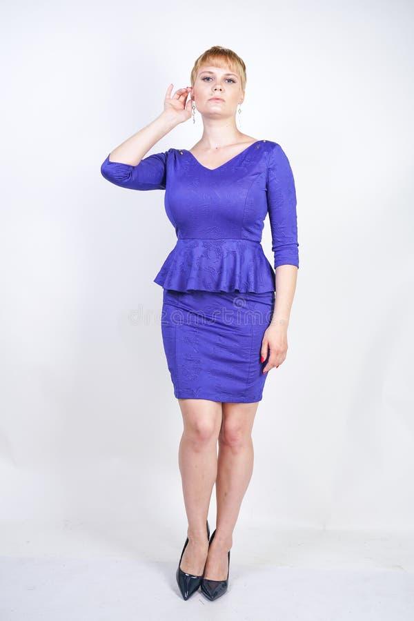 有短发的美丽的白种人女孩和在企业样式的蓝色中等长度礼服打扮的正大小身体与peplum在t 免版税图库摄影
