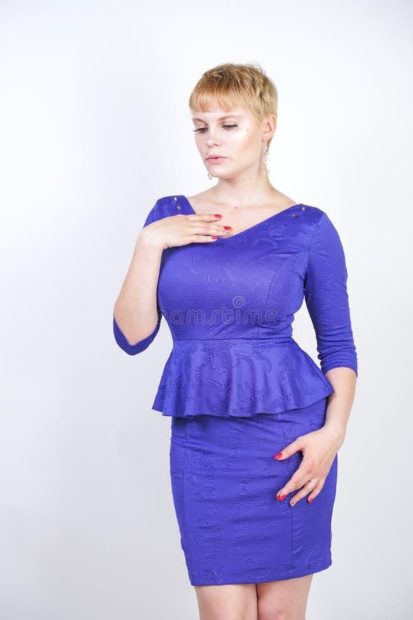 有短发的美丽的白种人女孩和在企业样式的蓝色中等长度礼服打扮的正大小身体与peplum在t 库存图片