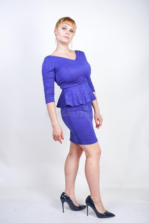 有短发的美丽的白种人女孩和在企业样式的蓝色中等长度礼服打扮的正大小身体与peplum在t 免版税库存图片