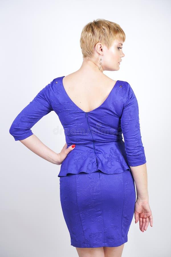 有短发的美丽的白种人女孩和在企业样式的蓝色中等长度礼服打扮的正大小身体与peplum在t 图库摄影