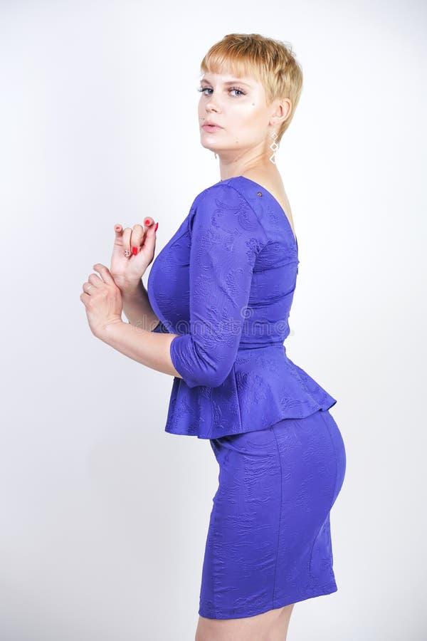 有短发的美丽的白种人女孩和在企业样式的蓝色中等长度礼服打扮的正大小身体与peplum在t 库存照片