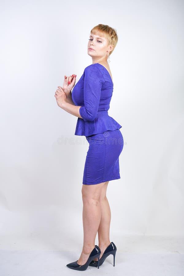 有短发的美丽的白种人女孩和在企业样式的蓝色中等长度礼服打扮的正大小身体与peplum在t 免版税库存照片