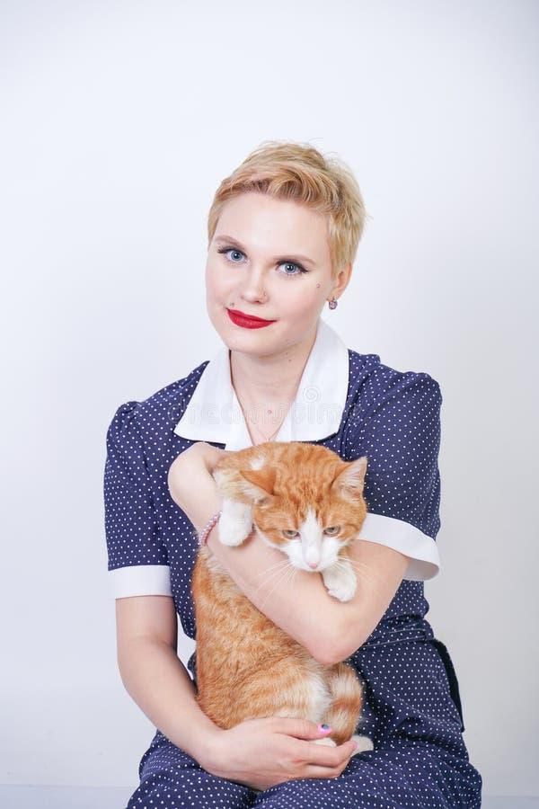 有短发的逗人喜爱的亲切的妇女在画报拿着她在白色背景的圆点礼服心爱的宠物在演播室 正大小广告 库存照片