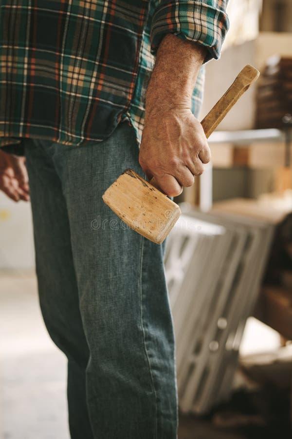 有短槌锤子的木匠在车间 免版税库存图片