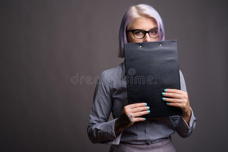 有短的五颜六色的头发的年轻美丽的女实业家反对g 免版税库存照片