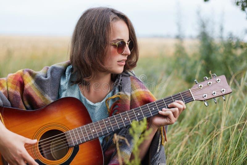 有短的发型的美丽的女性戴时髦的太阳镜休息户外弹吉他享受她的暑假的 fe 库存照片