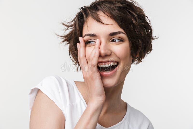 有短的棕色头发的在基本的T恤杉微笑和接触她的面孔用手的愉快的妇女画象  库存图片
