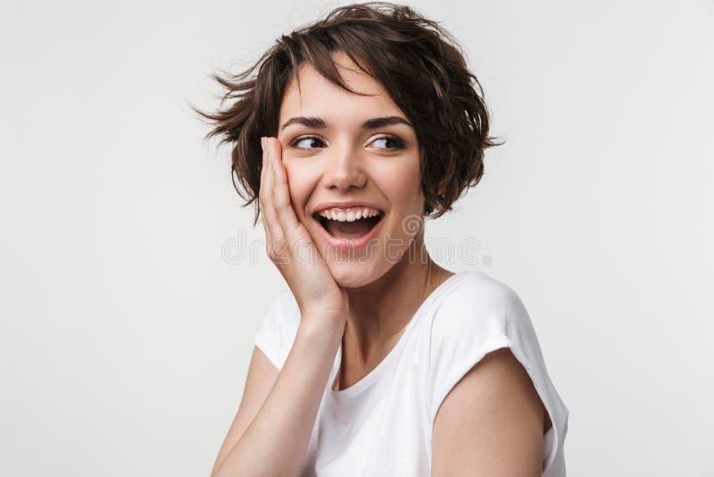 有短的棕色头发的在基本的T恤杉微笑和接触她的面孔用手的美女画象  免版税库存图片