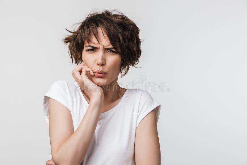 有短的棕色头发的在基本的T恤杉皱眉和看照相机的害怕妇女画象  免版税库存图片