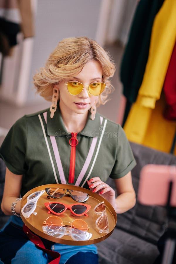 有短的波浪发的白肤金发的美发师摄制关于太阳镜的博克 库存图片