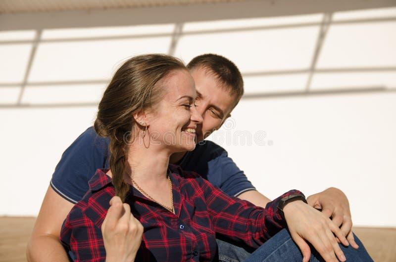有短的理发的人和有辫子和格子衬衫的女孩看彼此 免版税图库摄影