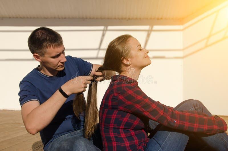 有短的理发的人把有长的黑发和格子衬衫的一个女孩编成辫子 免版税库存照片
