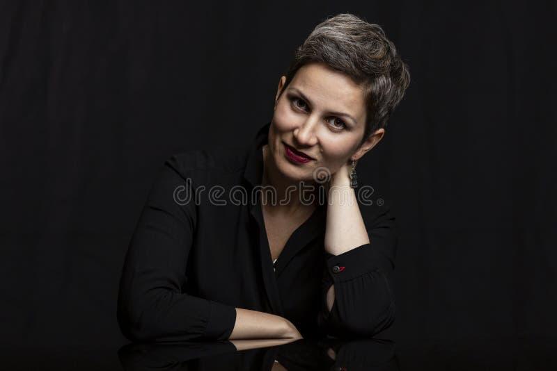 有短的理发的微笑的中年妇女,特写镜头 在黑背景的画象 免版税库存照片