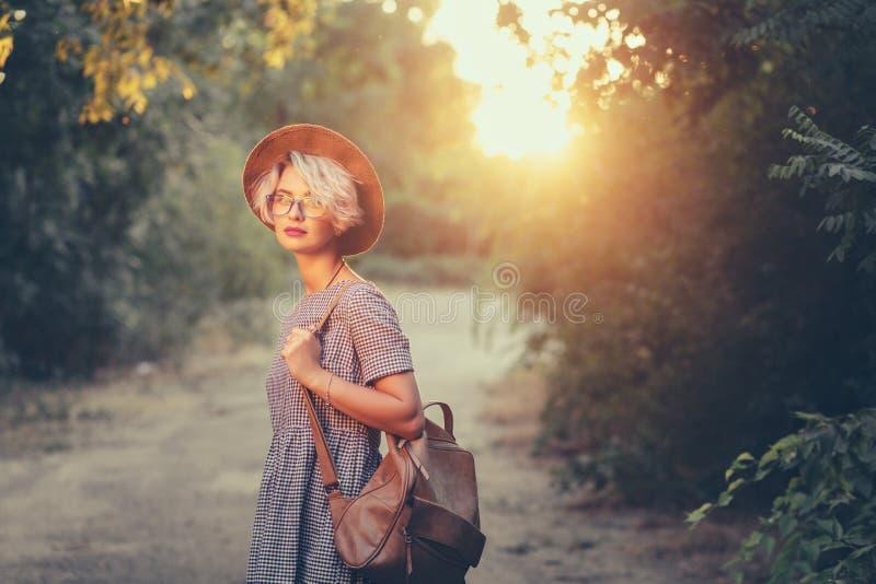 有短的理发的逗人喜爱的白肤金发的女孩走与袋子在日落背景的森林里 r 库存图片