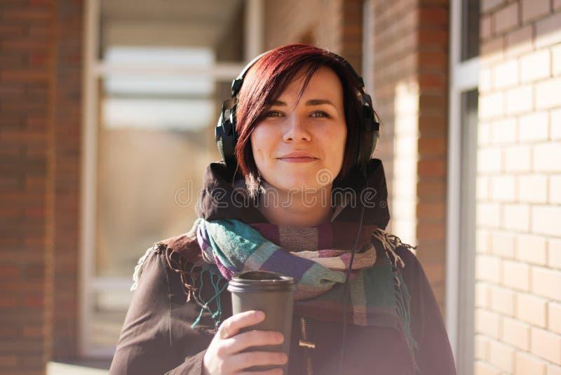 有短的红色头发和耳机的年轻美丽的妇女用去的咖啡杯子 免版税库存图片