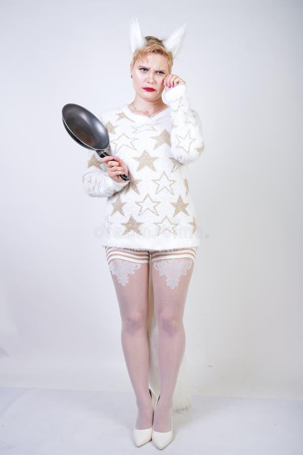有短的金发的一个恼怒的女孩在有毛皮耳朵的一件蓬松毛线衣 有黑空的煎锅的在手中o邪恶的正大小妇女 免版税库存照片