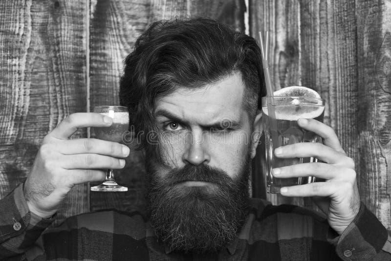 有短的鸡尾酒的男服务员在严密的面孔,木背景 英俊的侍酒者画象在工作 有短小的男服务员 库存图片