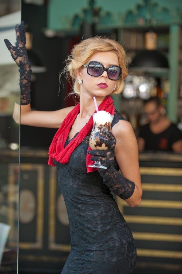 有短的黑鞋带礼服和红色围巾和高跟鞋的,室外射击时兴的夫人 年轻可爱的短发金发碧眼的女人 免版税图库摄影