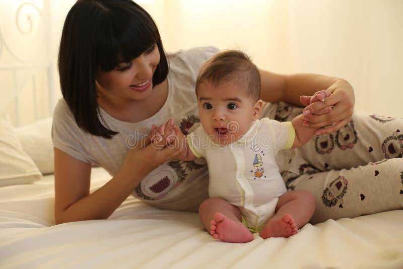 有短的黑发和她的小逗人喜爱的男婴的美丽的母亲 免版税图库摄影
