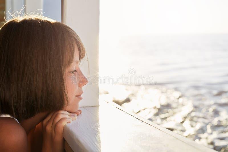 有短的黑发的小孩,看从船甲板,赞赏的风平浪静,当休息在她的暑假期间时 豆杆 图库摄影