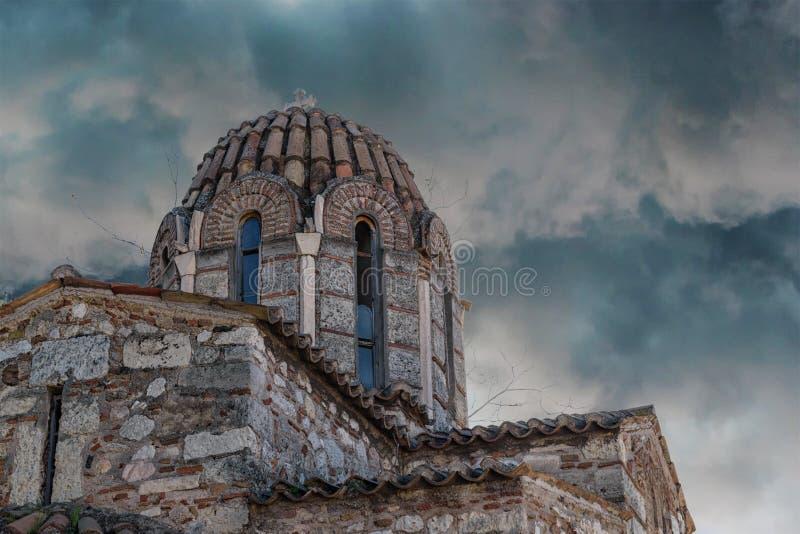 有石十字架的老希腊教会在黑暗的天空背景  免版税库存照片