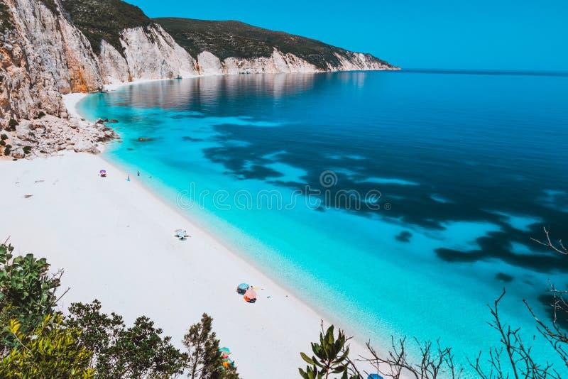 有石灰石岩石海岸线的, Kefalonia,希腊晴朗的田园诗Fteri海滩盐水湖 游人放松在伞下近 库存照片