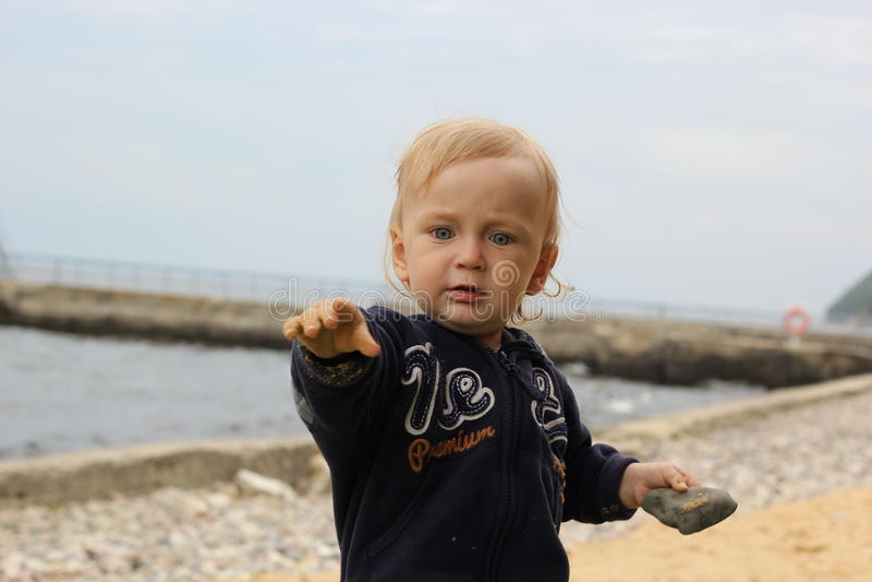 有石头的小男孩 免版税库存图片