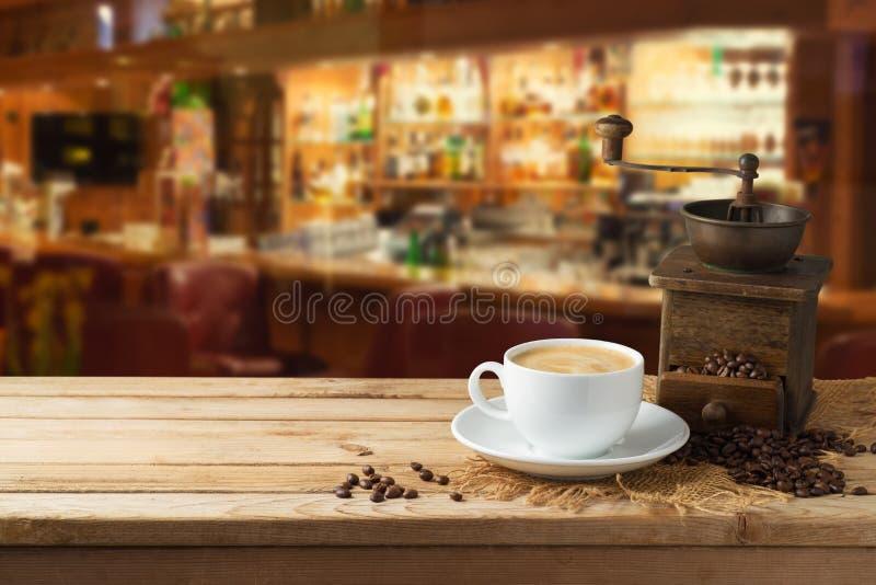 有研磨机磨房的咖啡杯在餐馆int的木桌上 库存图片