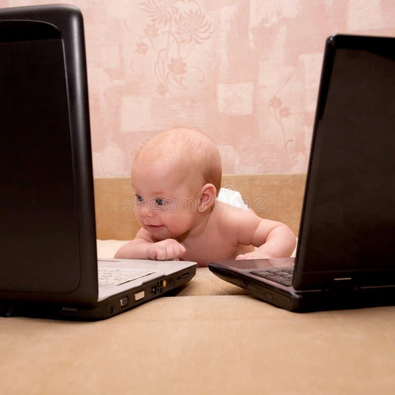 有研究二台膝上型计算机的蓝眼睛的婴孩 库存图片