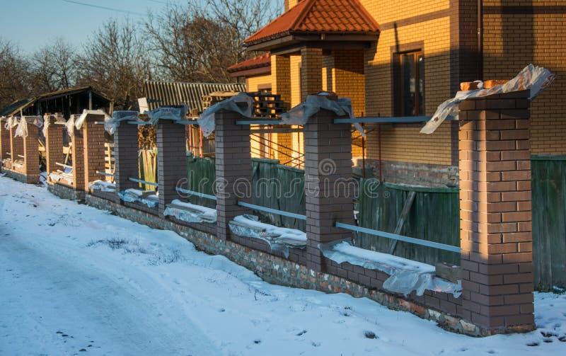 有砖专栏的未完成的篱芭 库存图片