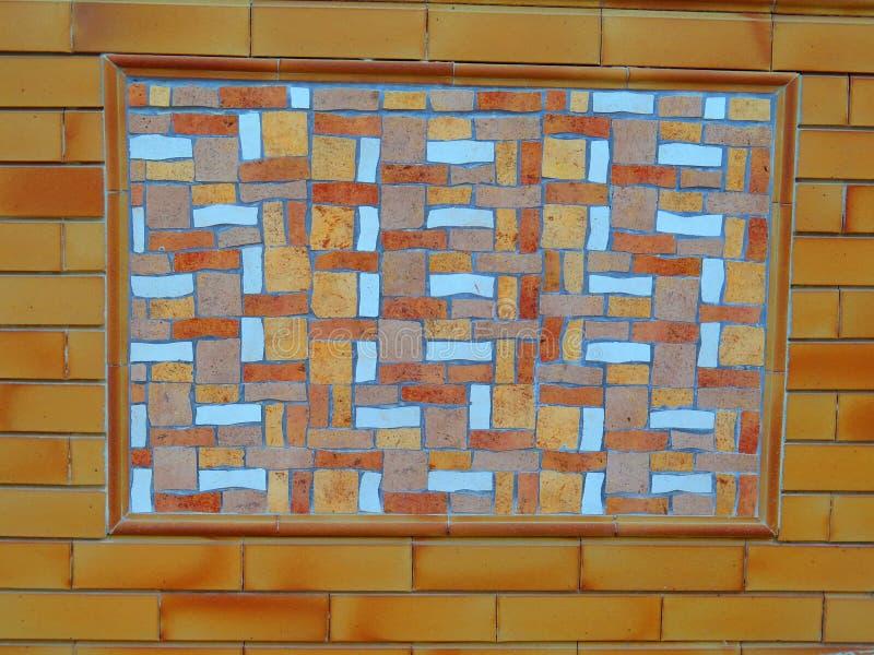 有砖周围和五颜六色的石插入物的墙壁 库存图片