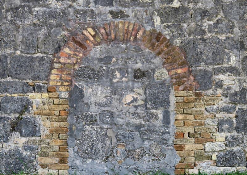 有砖曲拱的石墙 库存照片