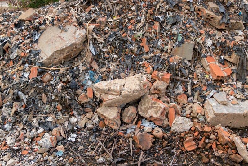 有砖的肮脏的建筑废品旧货栈,混凝土,水泥墙壁-回收为环境的垃圾垃圾-塑料废物 免版税库存图片