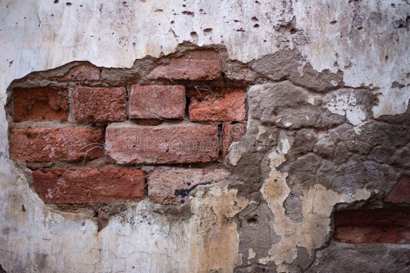 有砖纹理的脏的涂灰泥的墙壁 图库摄影