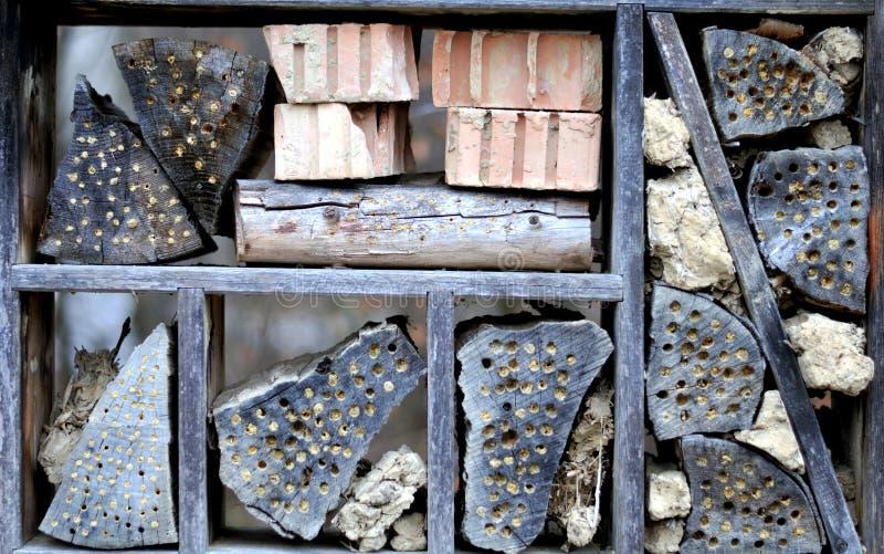 有砖,黏土丛和木日志的昆虫旅馆 免版税库存照片